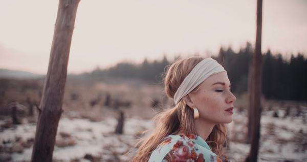 Profile shot of a boho girl wearing a headband and sitting Royalty-free stock video