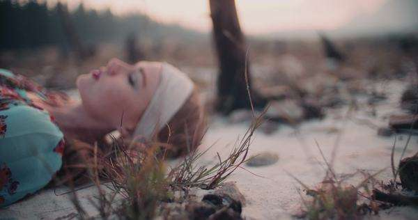 Portrait of a boho girl wearing vintage dress and jewelry lying down on sandy ground in slow motion Royalty-free stock video
