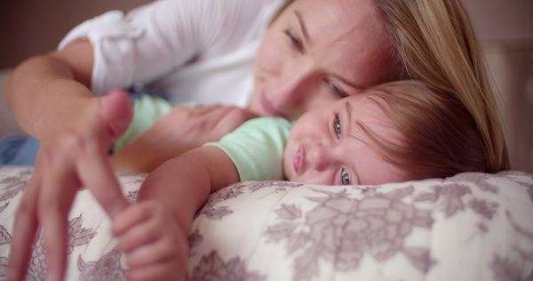 Crawling baby boy with blue eyes bonding with his mother during play time on the bed at home Royalty-free stock video