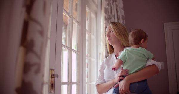 Mother standing with her baby boy at a window at home, serious or sad look on her face Royalty-free stock video