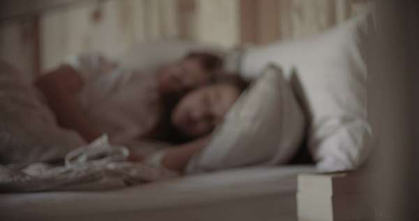 Young sleeping couple in bed, blurred as background Royalty-free stock video