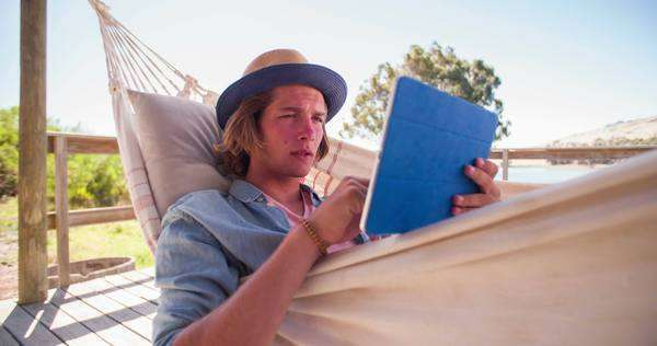 Teen guy relaxing in a hammock while reading on his digital tablet, panning in slow motion Royalty-free stock video