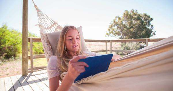 Teen girl using a digital tablet while relaxing in a hammock near a lake, panning in slow motion Royalty-free stock video