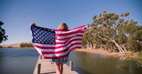 Girl running in slow motion with American flag on lake jetty Royalty-free stock video