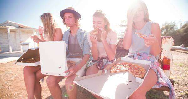 Teen friends sitting outside enjoying pizza and laughing together on a bright summer day Royalty-free stock video