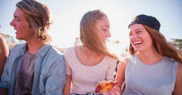 Sun flare heavy shot of teens eating pizza outdoors on a summer day, panning in slow motion Royalty-free stock video