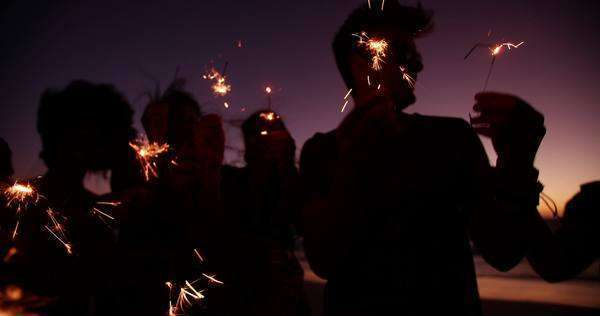 Group of friends having a beach party together and celebrating with sparklers in the  twilight in slow motion Royalty-free stock video