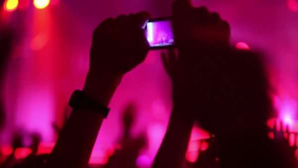 Hands hold camera with digital display among people at rave party with pink red light, view from behind Royalty-free stock video