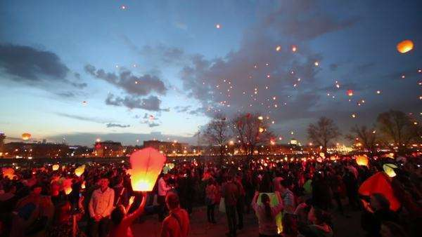 People launch many lanterns which fly to night sky against floating clouds Royalty-free stock video