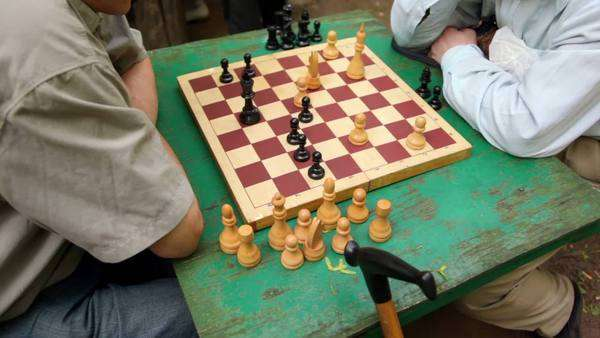 Two men sit and think under chessboard, closeup view of table Royalty-free stock video