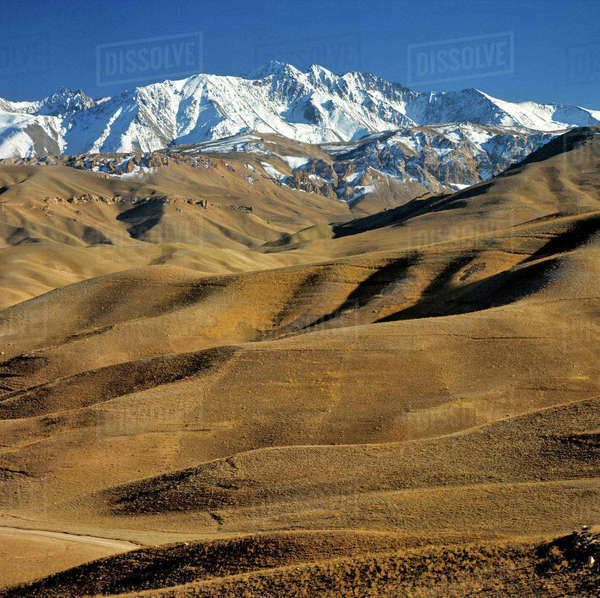 Afghanistan, Bamian Valley. Rolling hills lead to the snow fields of the rugged Hindu Kush Mountains near Bamian Valley, Afghanistan. Royalty-free stock photo