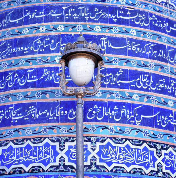 Afghanistan, Herat. An ornate street lamp stands out against the blue-tiled wall of the Friday Mosque, or Masjid-i-Jami, in Herat, Afghanistan. Royalty-free stock photo