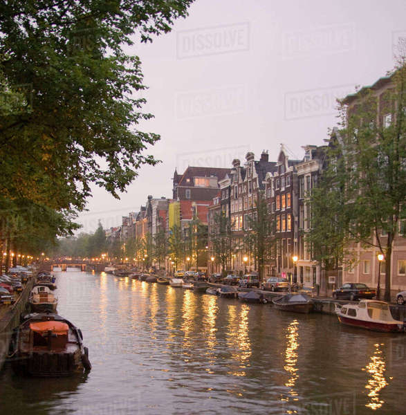 Street lights reflect onto the boat lined canal at dusk Royalty-free stock photo