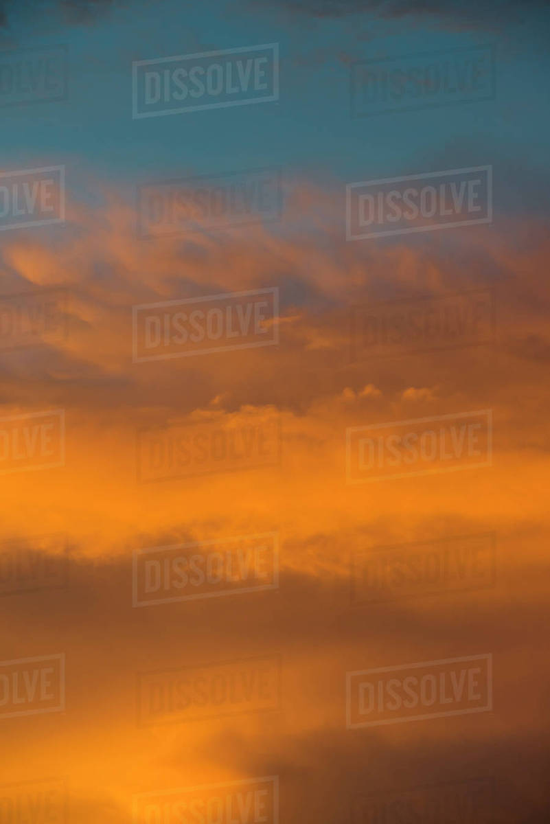 clouds reflecting the orange sunset colors against the blue twilight