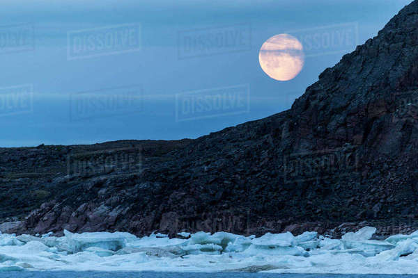 Canada, Nunavut, Territory, Moonrise above melting sea ice along Frozen Strait in northern Hudson Bay near Arctic Circle Rights-managed stock photo