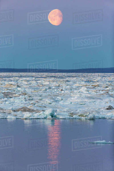 Canada, Nunavut, Territory, Moonrise above drifting sea ice along Frozen Strait in northern Hudson Bay near Arctic Circle Rights-managed stock photo