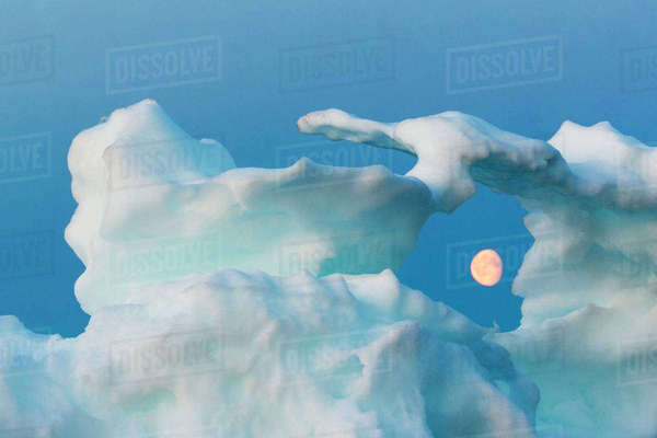 Canada, Nunavut, Territory, Moonrise framed in arch of melting iceberg along Frozen Strait in northern Hudson Bay near Arctic Circle Rights-managed stock photo