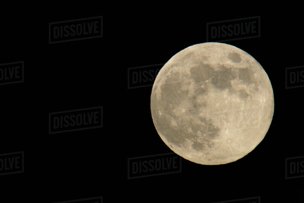 full moon with yellowish hue to right of frame stock photo dissolve