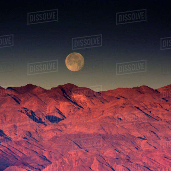 Moonset over Cottonwood Mountains at Sunrise, Death Valley National Park, California, USA. Rights-managed stock photo