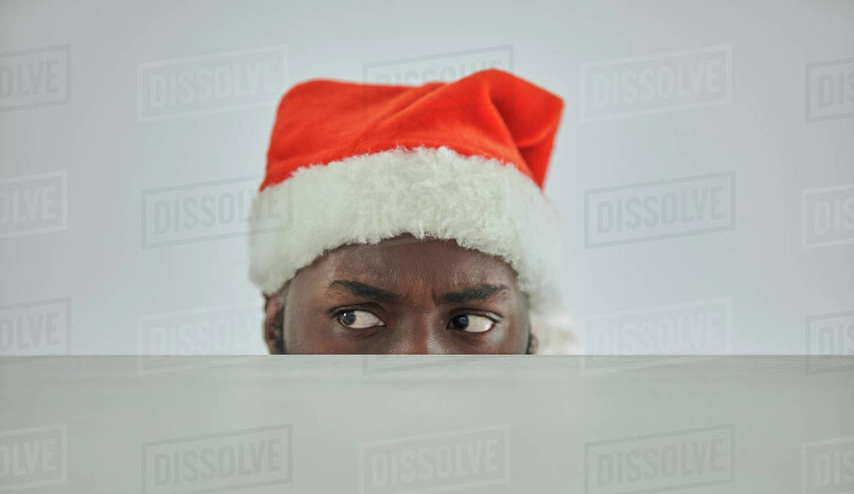 The african man in the santa hat watching from the table Royalty-free stock photo