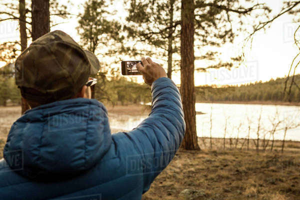 Man taking photograph of lake with smartphone Royalty-free stock photo