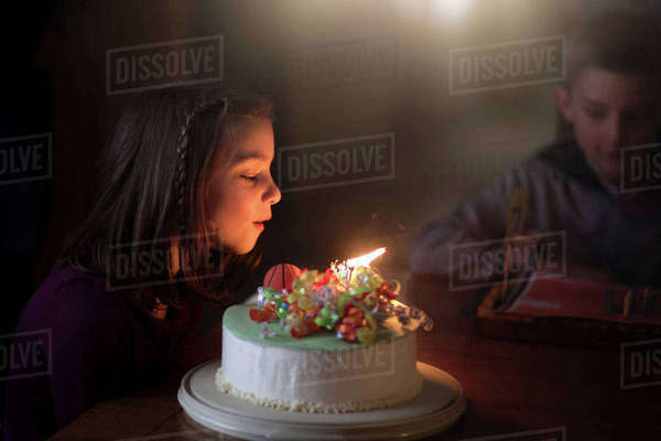 Girl blowing out candles on birthday cake Royalty-free stock photo