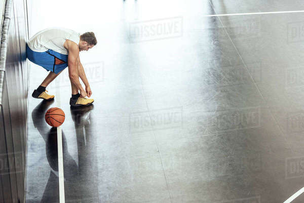 Male basketball player tying trainer laces on basketball court Royalty-free stock photo