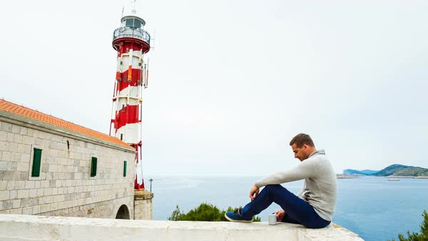 WS Man sitting with cup by lighthouse looking at view Royalty-free stock video