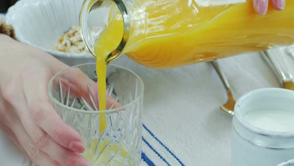 CU Woman pouring orange juice into glass at breakfast Royalty-free stock video