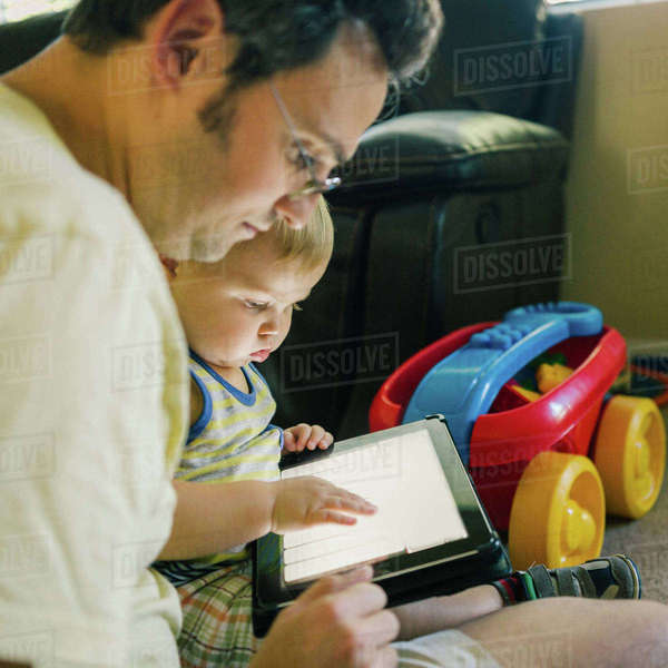 Father and young son looking at digital tablet Royalty-free stock photo