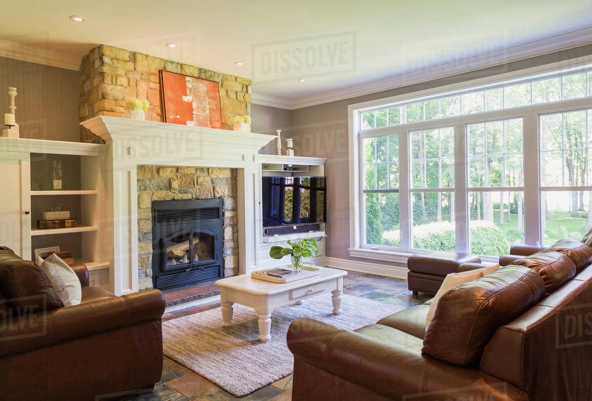 Brown leather sofa, sitting chairs and natural stone fireplace in  D25_106_618