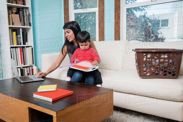 Woman using laptop while toddler son looking at notebook on sofa Royalty-free stock photo