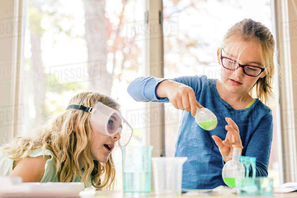 Two girls doing science experiment, shaking liquid in flask Royalty-free stock photo