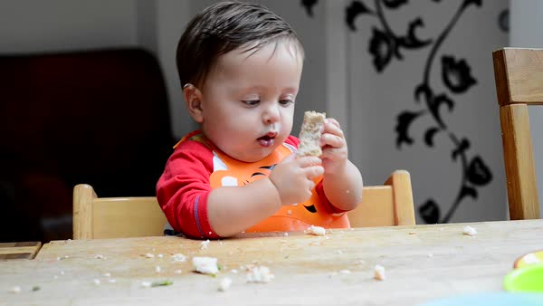 Baby boy (2-5 months) eating and playing with food Royalty-free stock video