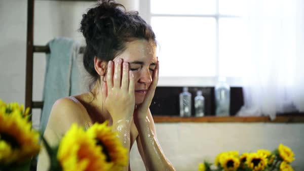 Young woman washing face in bathroom with sunflowers Royalty-free stock video