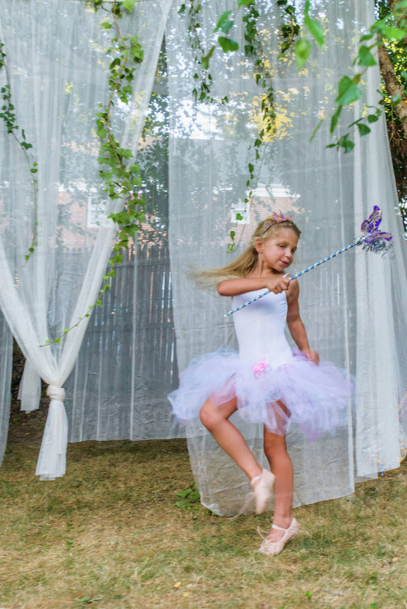Portrait of young girl, dressed as fairy, holding butterfly wand Royalty-free stock photo