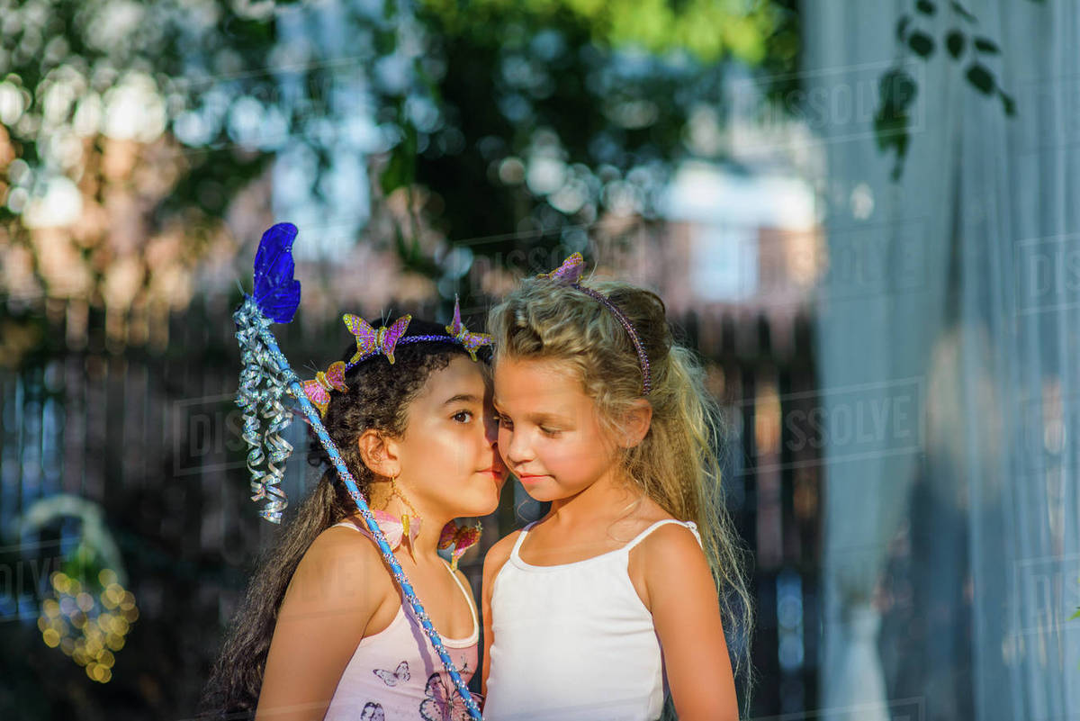 Two young girls dressed as fairies, girl whispering in friend's ear Royalty-free stock photo