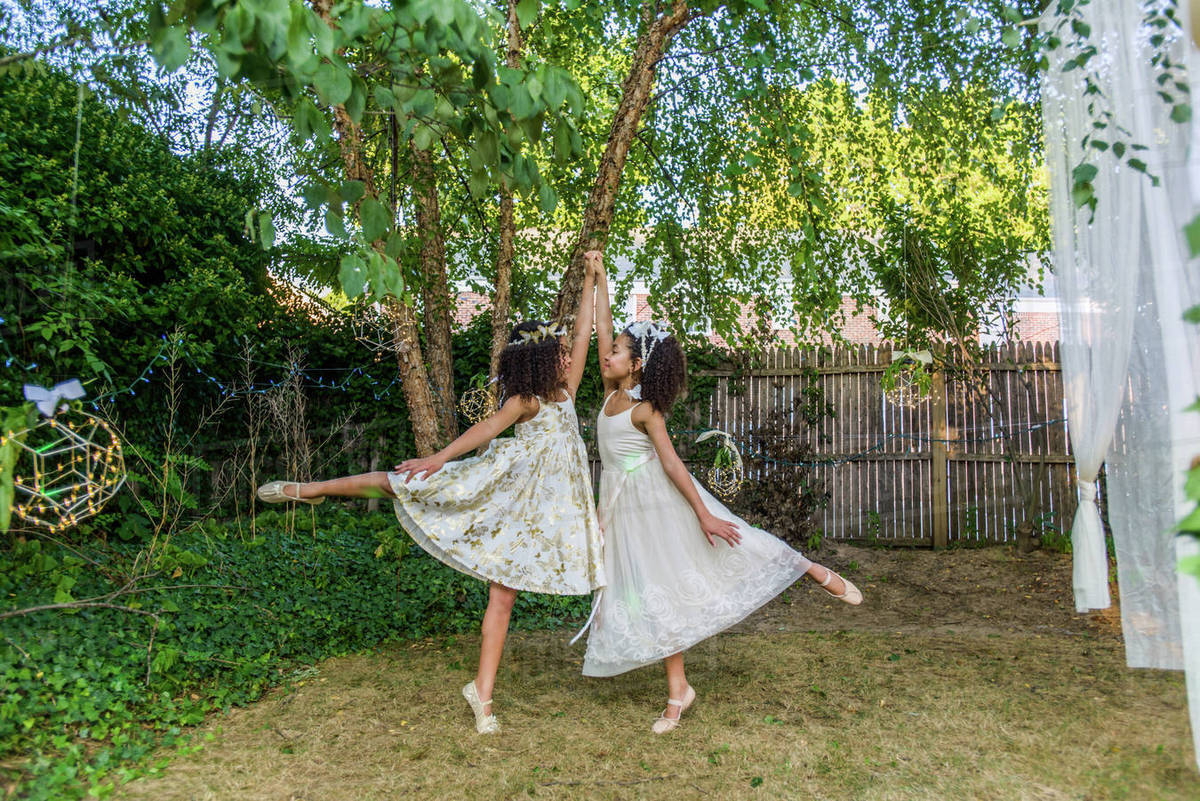 Two young girls, dressed as fairies, dancing outdoors Royalty-free stock photo