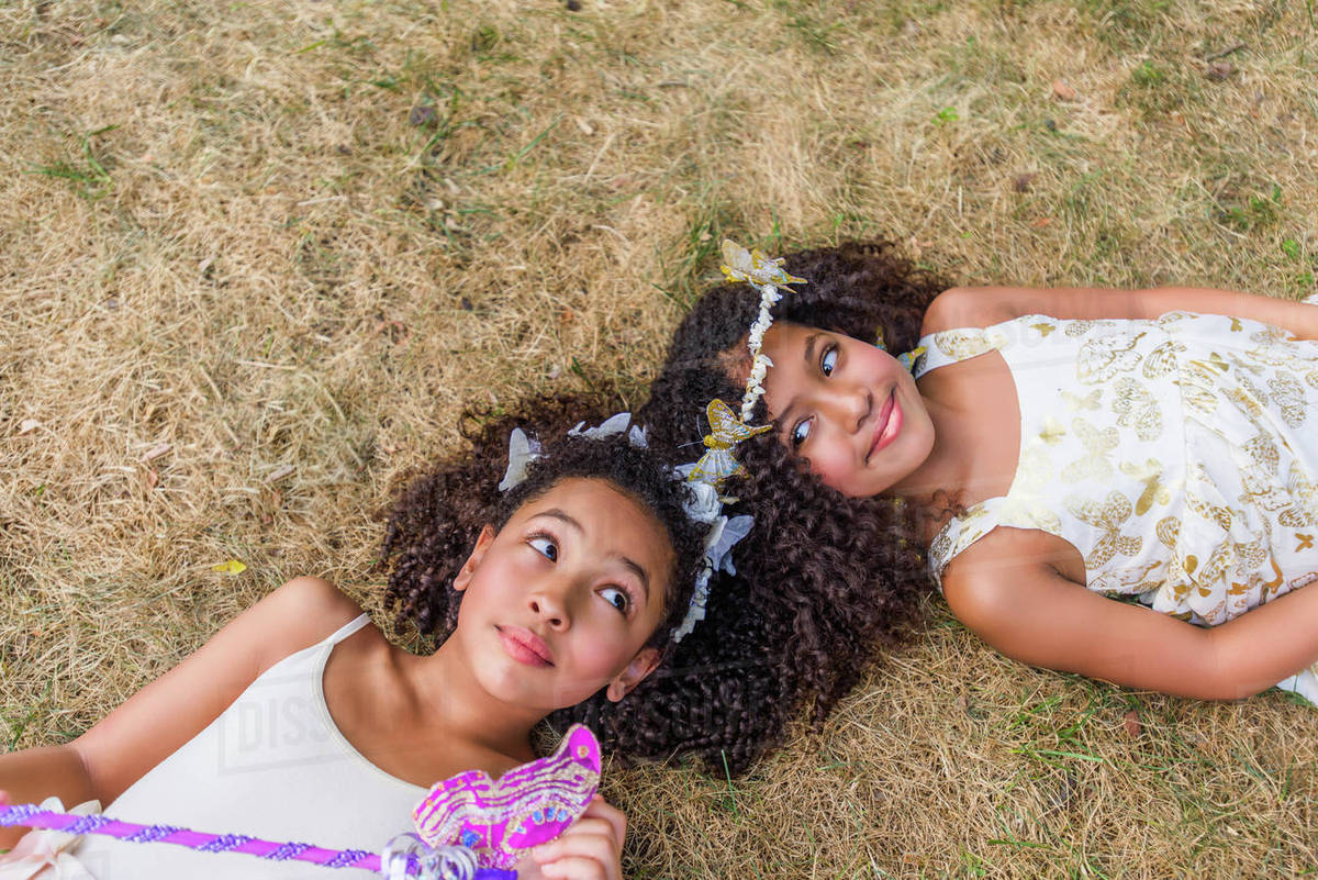 Two young girls, dressed as fairies, lying on grass, touching heads Royalty-free stock photo