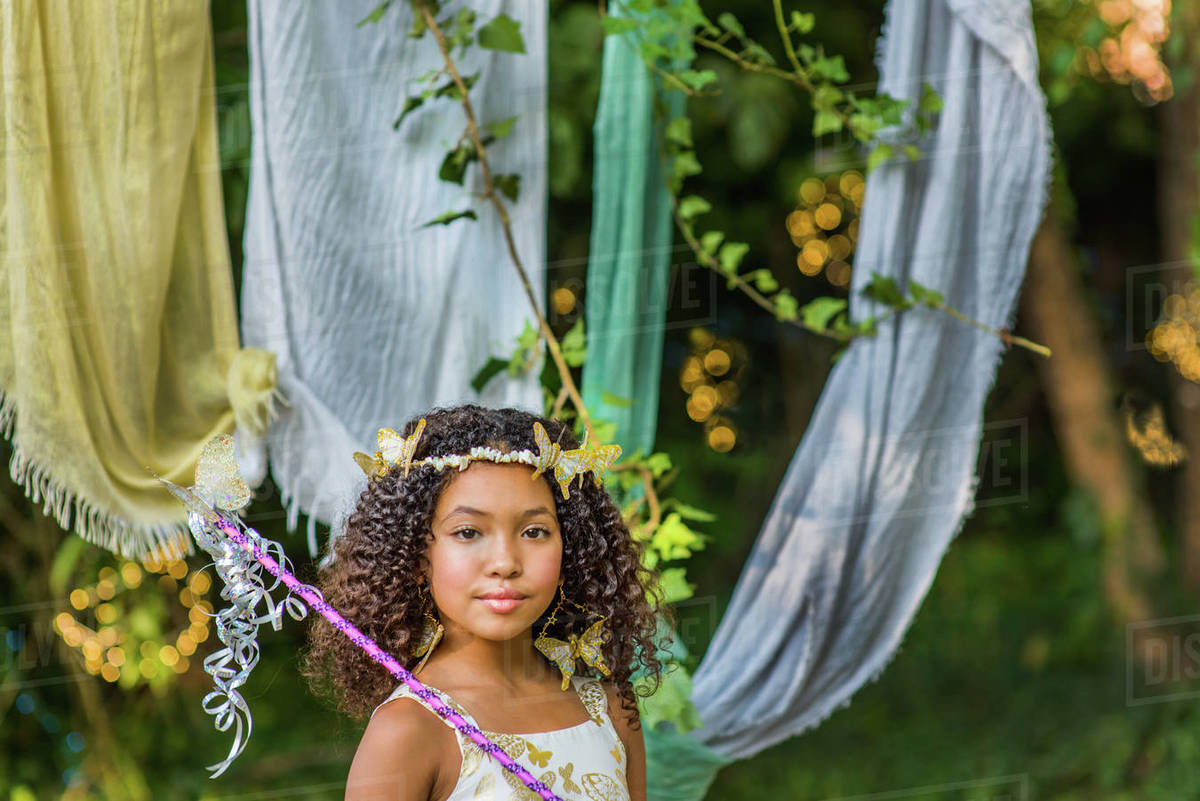 Portrait of young girl dressed as fairy, holding wand Royalty-free stock photo