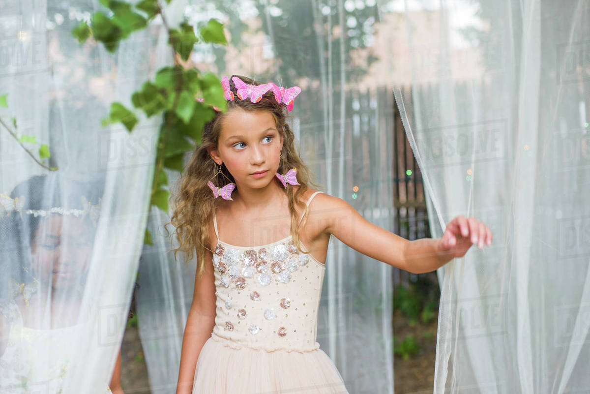 Portrait of young girl dressed as fairy, walking through sheer material Royalty-free stock photo