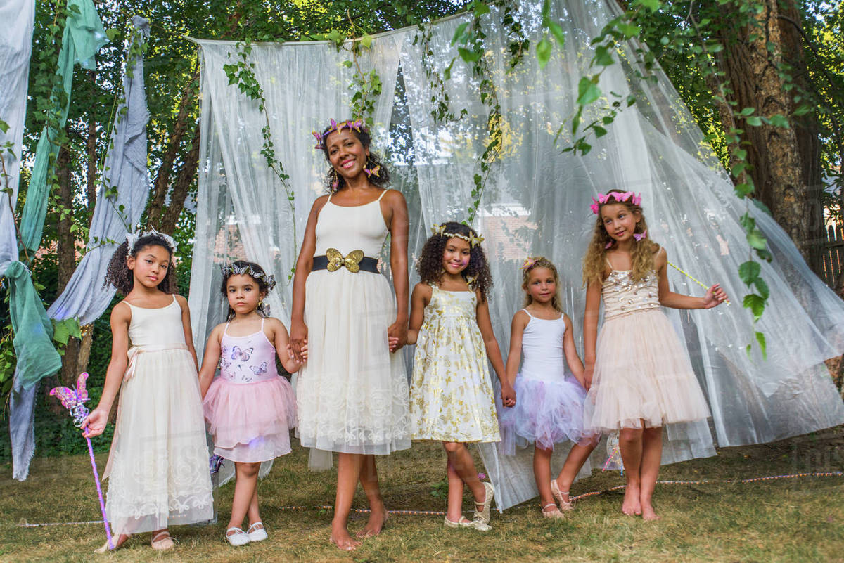 Portrait of mature woman with group of young girls, dressed as fairies, outdoors Royalty-free stock photo
