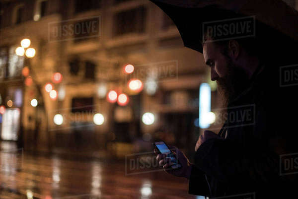 Mid adult man walking in city at night, using umbrella, looking at smartphone, Downtown, San Francisco, California, USA Royalty-free stock photo