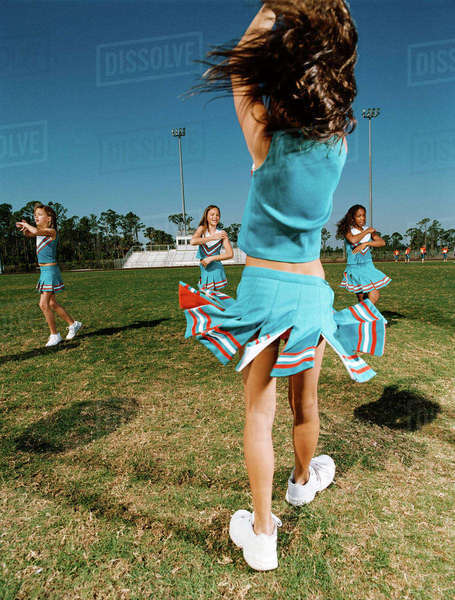 Cheerleaders performing dance routine on sports field Royalty-free stock photo