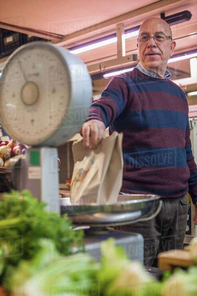 Shopkeeper weighing fresh produce in market Royalty-free stock photo