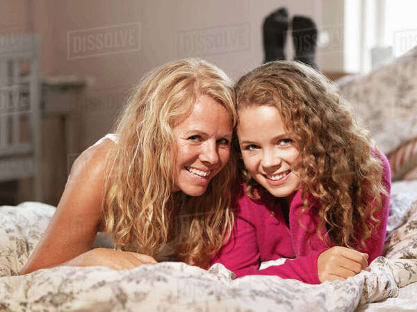 Young woman and mother relaxing together on bed, portrait Royalty-free stock photo