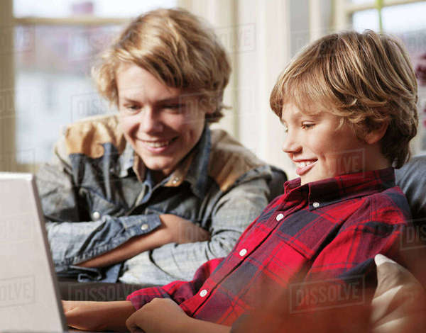 Teenage boy and brother watching laptop Royalty-free stock photo