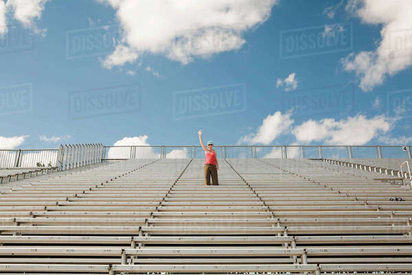 Mid adult woman waving in bleachers Royalty-free stock photo