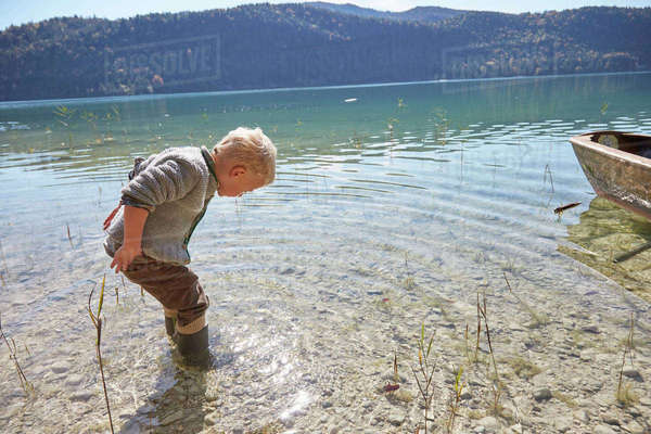 Boy paddling and looking down into lake, Kochel, Bavaria, Germany Royalty-free stock photo