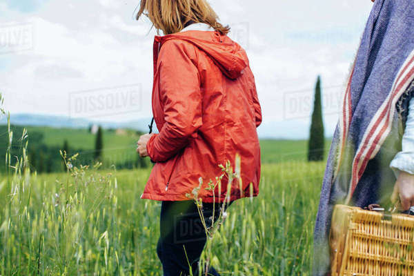 Cropped shot of two mature women strolling in wheatfield, Tuscany, Italy Royalty-free stock photo